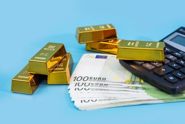 Золотые слитки, калькулятор и банкноты евро на синем столе. финансовое богатство или концепция сбережений.