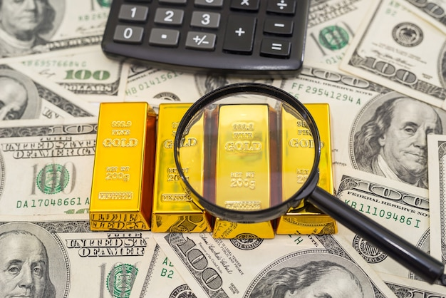 100枚の新しい米ドル紙幣の金の延べ棒、電卓、拡大鏡。ビジネスと金融の概念