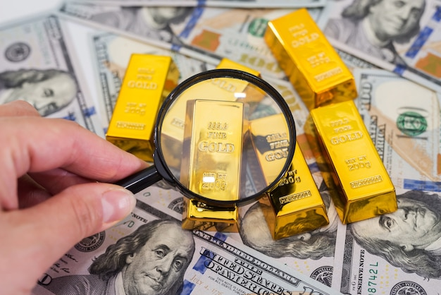 Gold bars on dollars with a magnifying glass. a hand with a magnifying glass checks the gold bar.