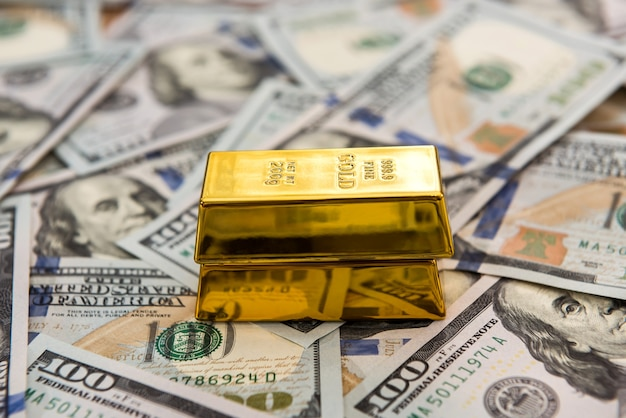 Gold bars lying on dollar bills money and save concept