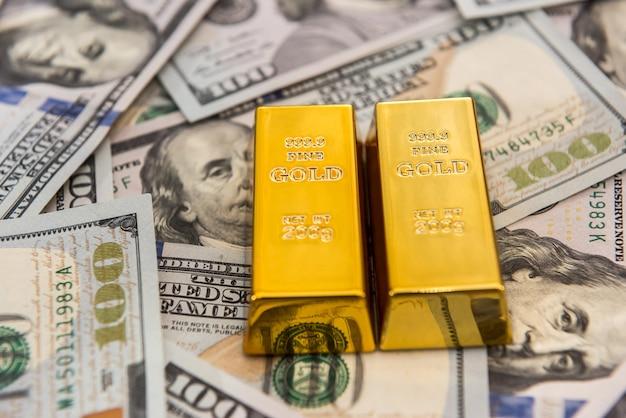 Золотые слитки, лежащие на долларовых купюрах, деньги и концепция экономии
