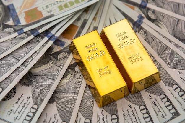 Золотые слитки, лежащие на долларовых купюрах. деньги и концепция экономии