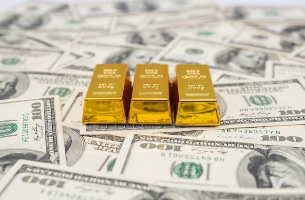 Золотые слитки на 100 новых банкнотах доллара сша. концепция бизнеса и финансов