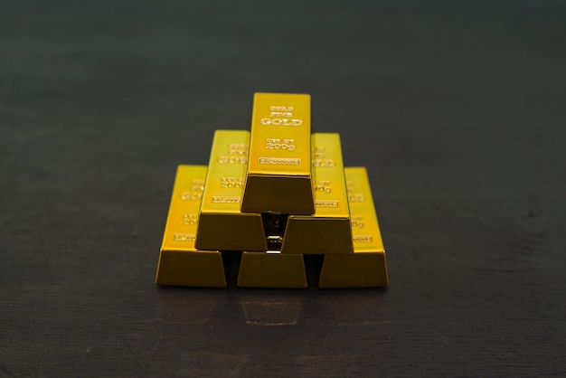 Золотые слитки на черном деревянном столе.