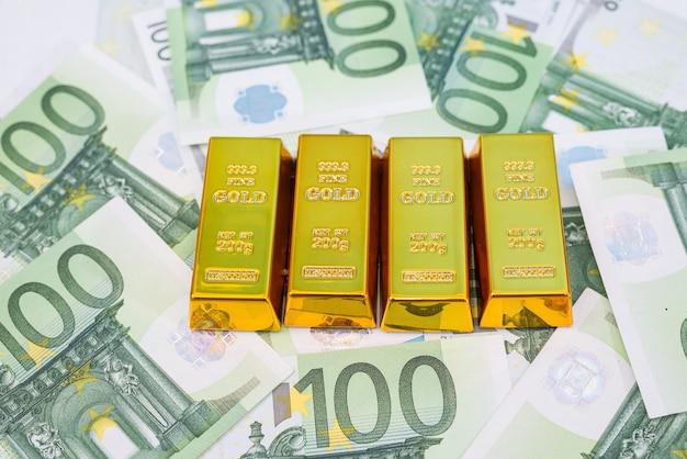 Золотые слитки на банкнотах евро. концепция финансового богатства или сбережений.