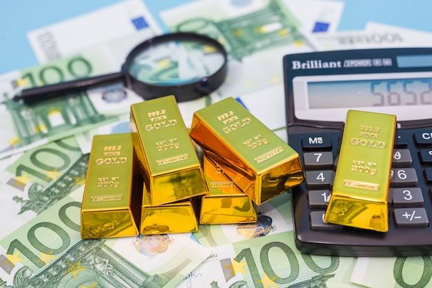 Золотые слитки с лупой, калькулятором и банкнотами евро. финансовое богатство или концепция сбережений.