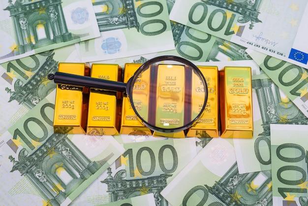 Золотые слитки с увеличительным стеклом над банкнотами евро. финансовое богатство или концепция сбережений.