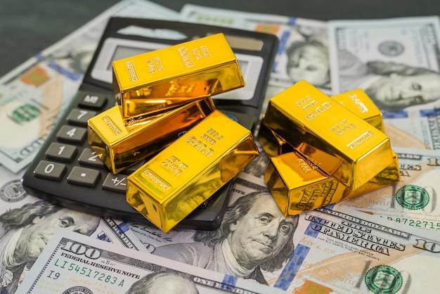 Золотые слитки с калькулятором и долларами на черном столе.