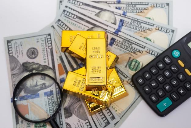 계산기와 100 개의 새로운 달러 지폐에 돋보기가있는 금괴. 비즈니스 및 금융 개념