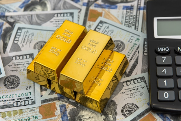 Gold bars with calculator lying on dollar bills