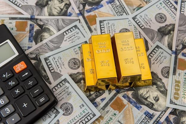 Золотые слитки с калькулятором на долларовых купюрах