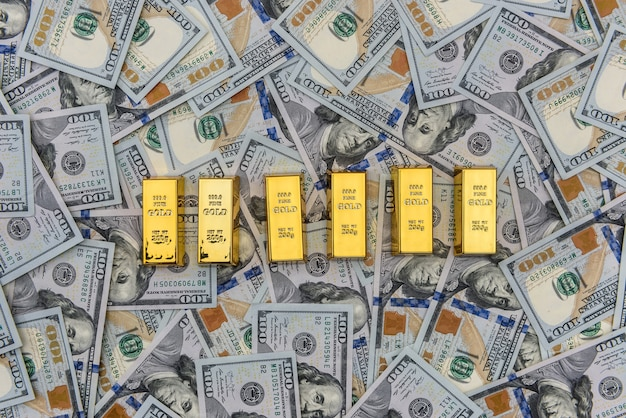 배경으로 100 달러 지폐와 금 괴
