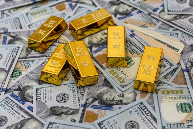 Золотые слитки с банкнотами в сто долларов