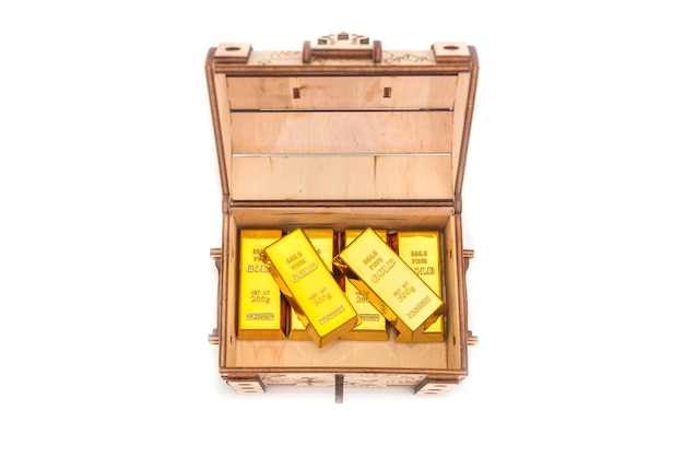 Gold bars in a wooden chest isolated.