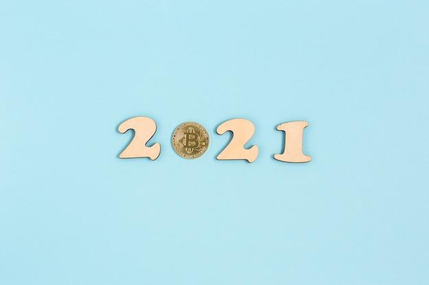 Золотой биткойн и деревянные цифры 2021 года лежит на синей поверхности