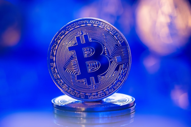 Gold bitcoin in blue neon light. physical btc coin. cryptocurrency or virtual money.