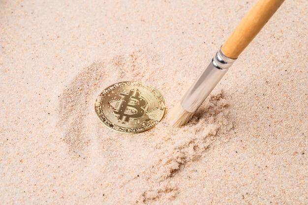 모래에 묻힌 금 비트코인. 암호화폐와 돈 프리미엄 사진
