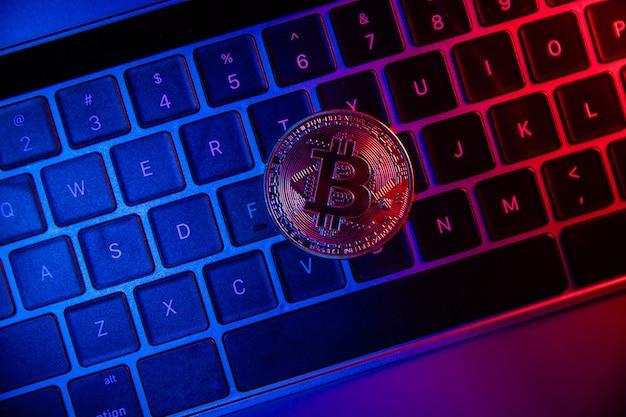 Золотая монета биткойн в неоне на клавиатуре. концепция инвестиций в криптовалюту.