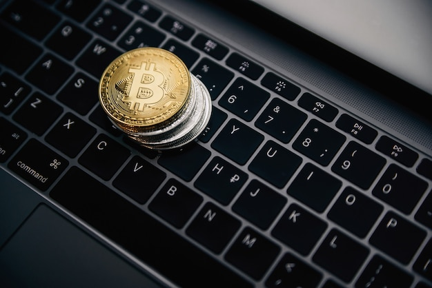 Gold bitcoin on the coins stack, digital money on computer keyboard. cryptocurrency business concept