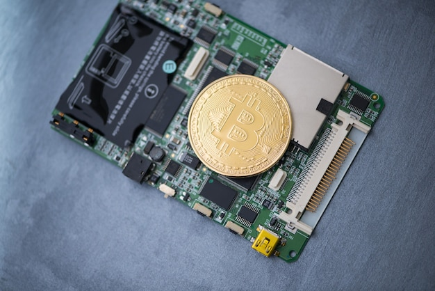 Gold bitcoin on a computer board, on a gray surface. electronic money