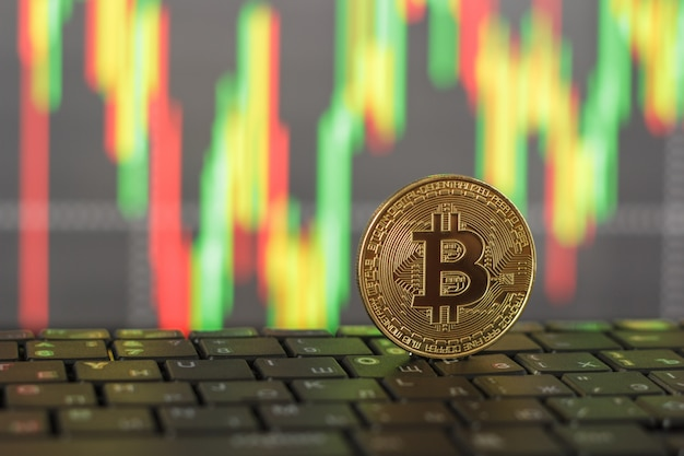 Gold bitcoin and keyboard close-up on blurred background