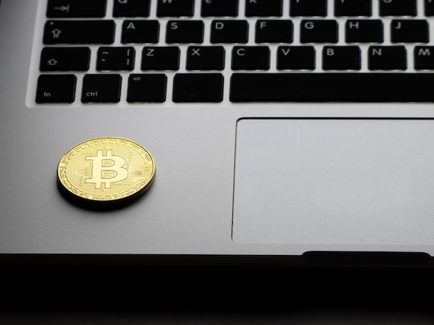 Gold bitcoin on the laptop keyboard at night.