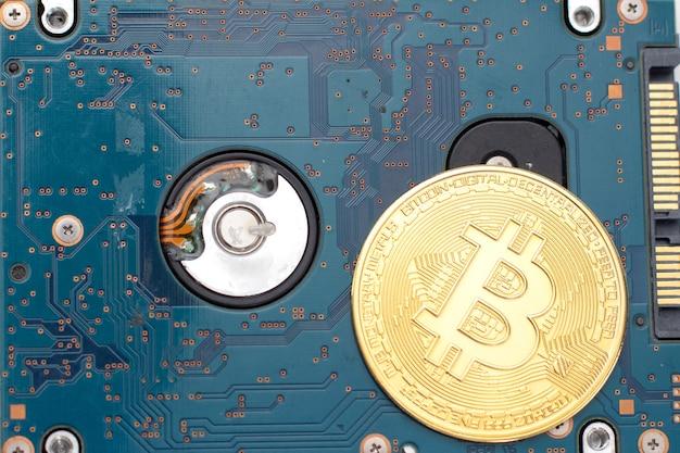 Золотой биткойн на жестком диске.