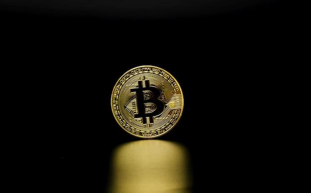 Золотой биткойн на черном фоне. криптовалютная монета