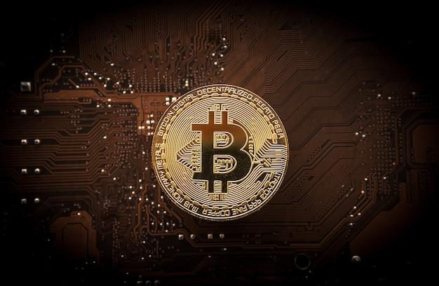 Золотой биткойн на плате компьютера, концепция добычи биткойнов.