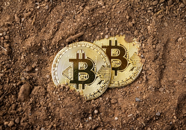 地面にゴールドビットコイン、マイニングビットコインのコンセプト。
