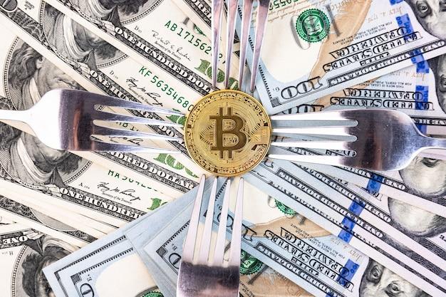 100ドル札とカトラリーの背景に金のビットコイン。