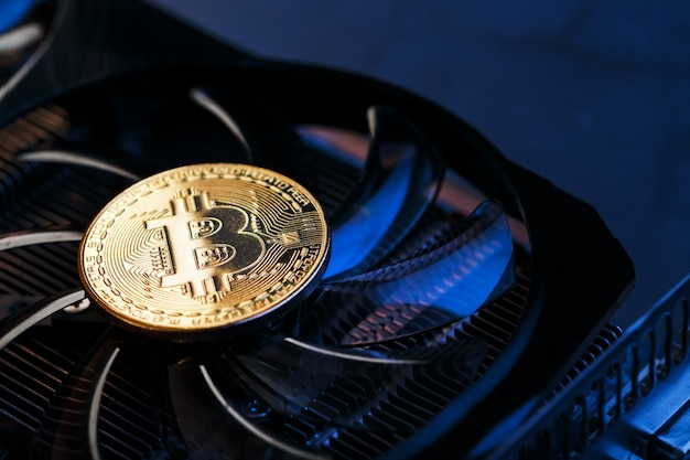 暗い背景の上面図のビデオカードクーラーの金ビットコイン
