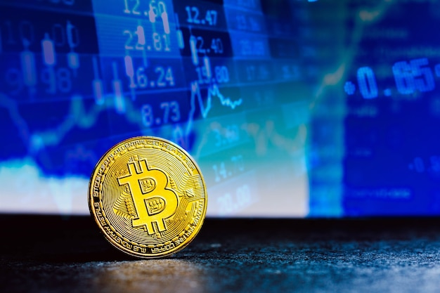 A gold bitcoin seen on display in the background a stock market graph