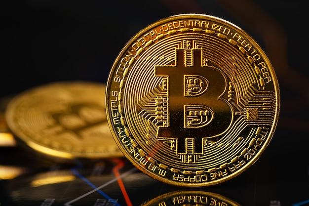 暗号通貨の値と価格に関する統計と財務チャートに立っているゴールドビットコイン。仮想通貨またはブロックチェーン暗号通貨。