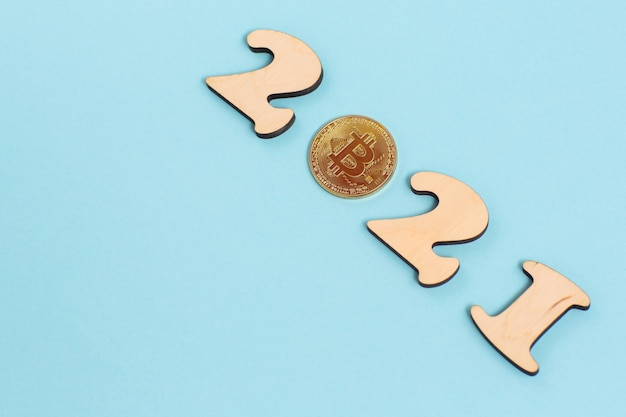 Gold bitcoin and wooden numbers 2021 lies on a blue surface