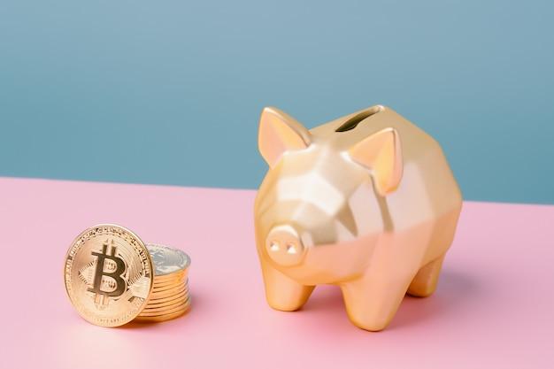 분홍색과 파란색 배경에 금색 비트코인과 금색 돼지 저금통. 암호화폐와 돈.
