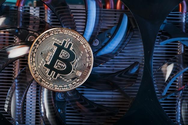 サイバーパンクのスタイルの青いバックライト付きのビデオカード上のゴールドビットコイン。暗号通貨。ビットコインマイニングの概念