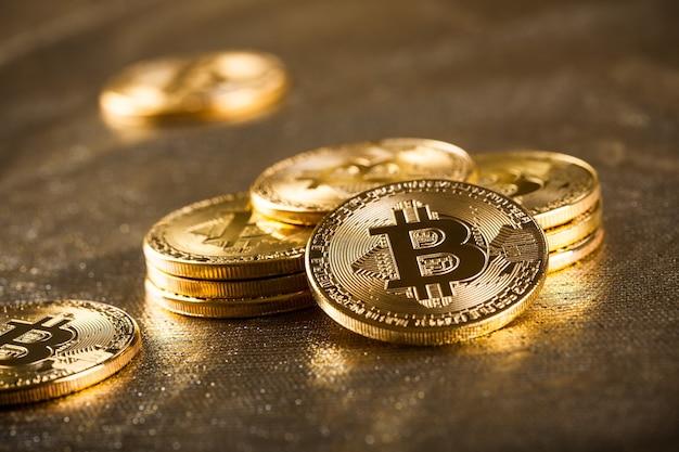 빛나는 배경에 금 bitcoins, 가까이