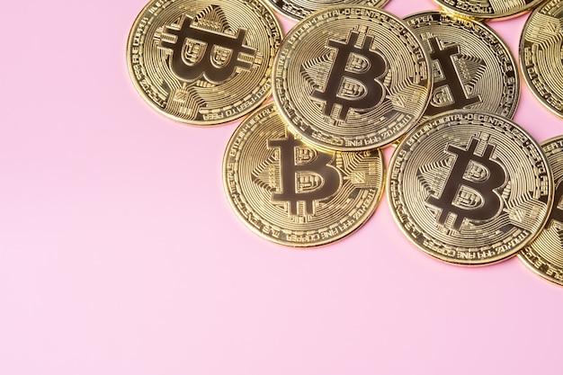 분홍색 배경에 금색 비트코인입니다. 암호화폐와 돈.