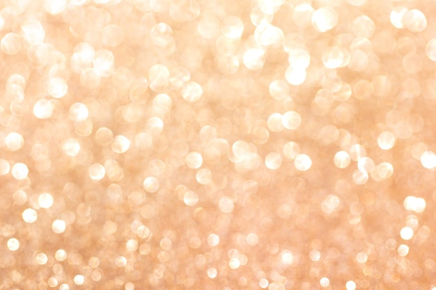 Gold blurred glitter background. sparkling and shiny texture for christmas and new year holiday or seasonal wallpaper decoration