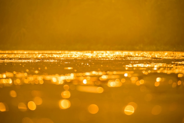 Gold bokeh on water surface with sunset background