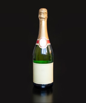 Gold bottle of champagne on black background for your christmas or new year project. empty space for the design or text on the label.