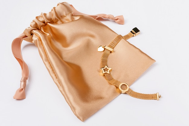 A gold bracelet on a golden silk gift bag