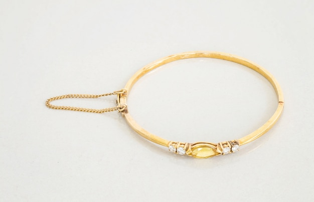 Gold bracelet on gray marble stone Premium Photo