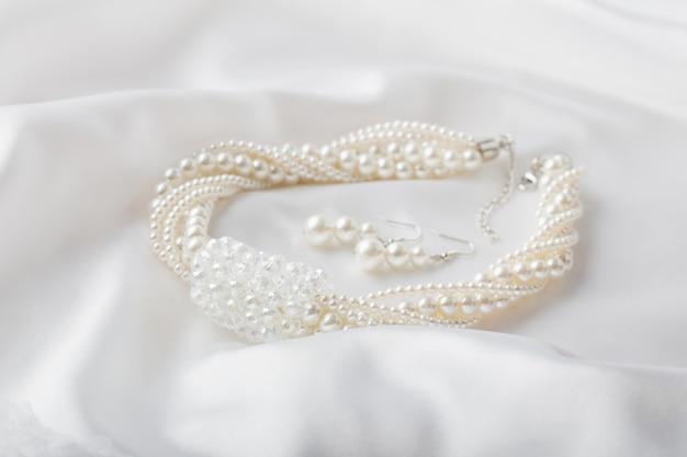 Золотой браслет на белой ткани