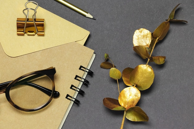 Gold branch, notes, glasses on grey background