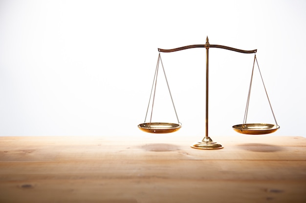 Gold brass balance scale on wooden desk and white backdrop, law and justice concept.