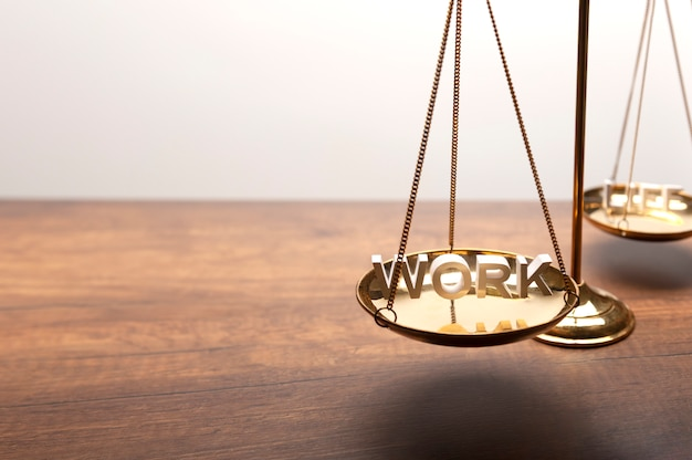 Gold brass balance scale on wooden desk with 3d text