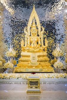 Золотая статуя будды перед роскошной предпосылкой.
