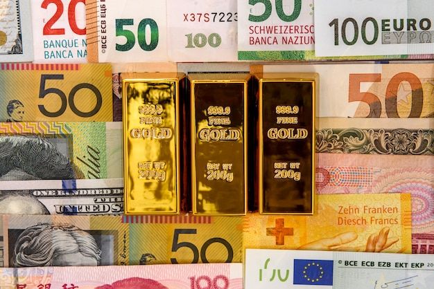 Gold bullion on colorful banknotes close up